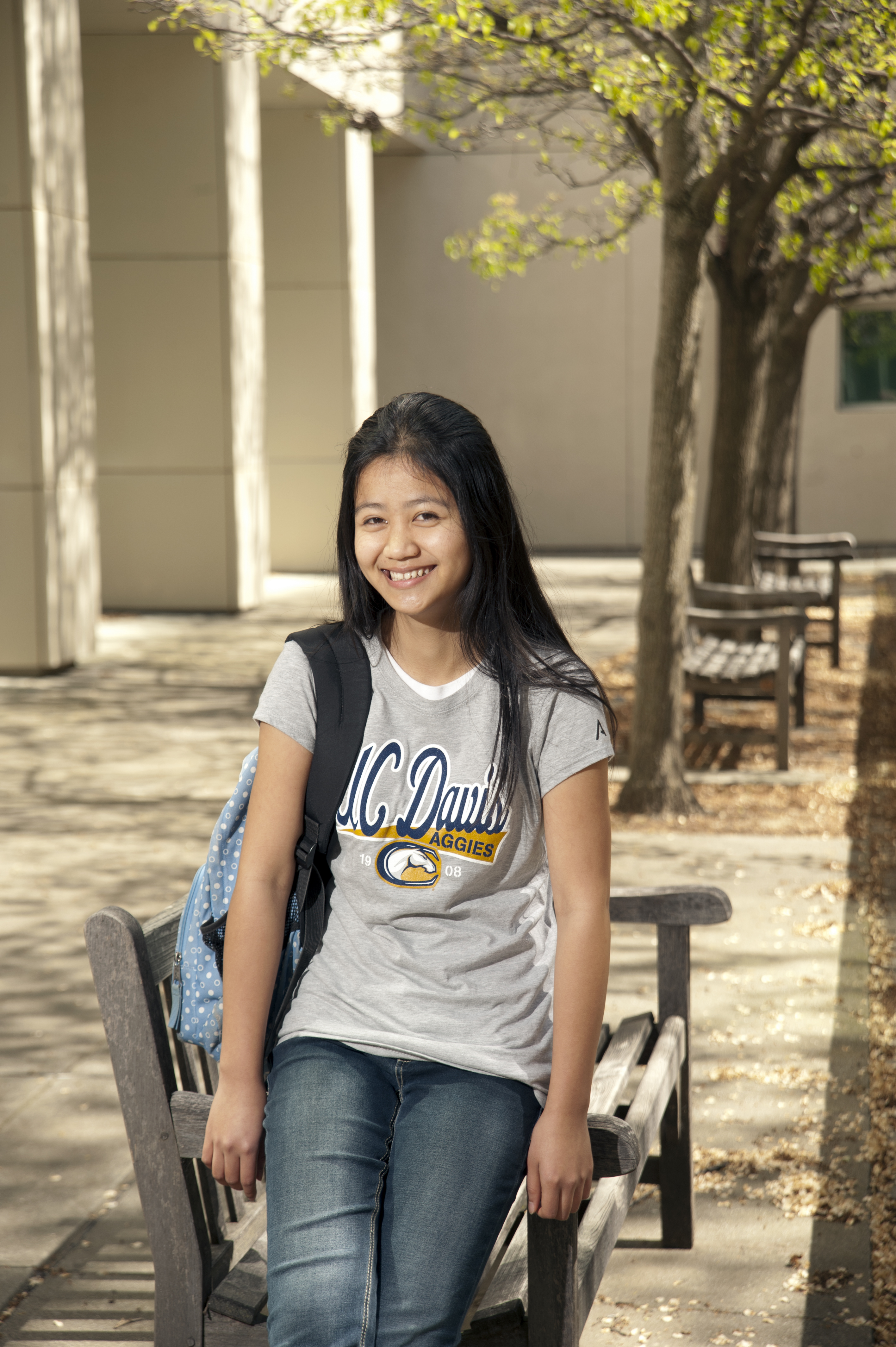 smiling student leaning against a bench