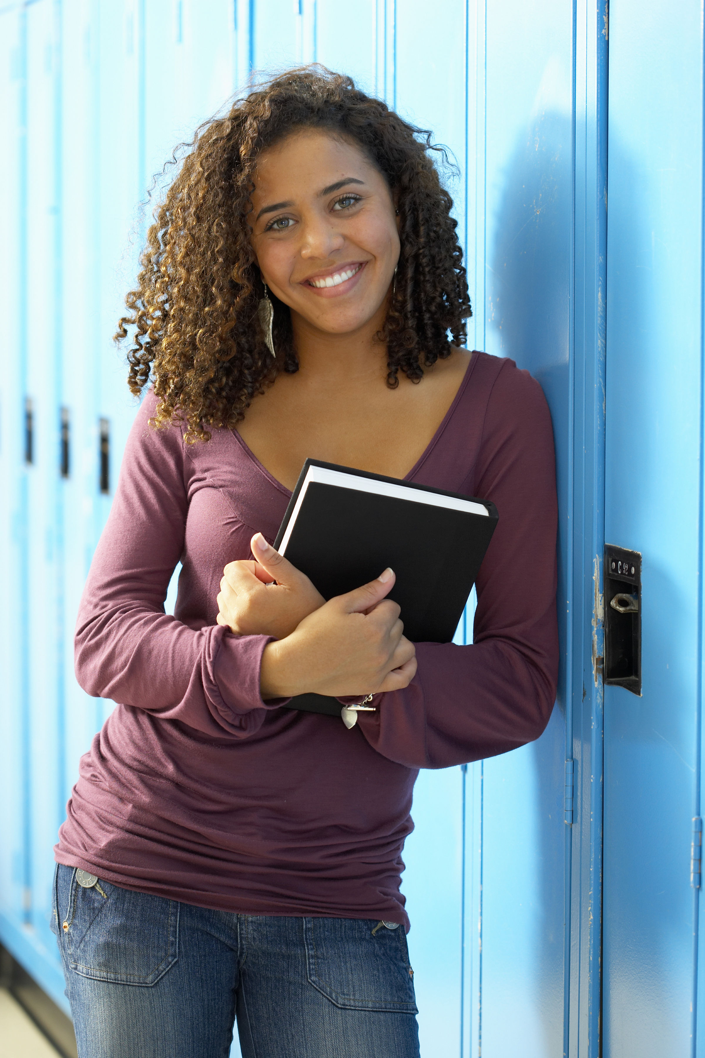 girl standing at a school locker holding a book