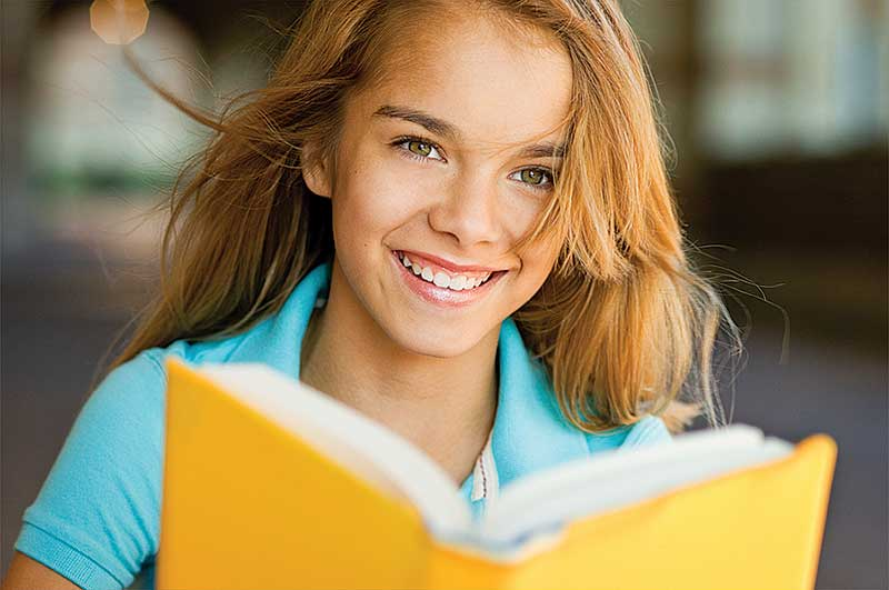 girl smiling and holding a book