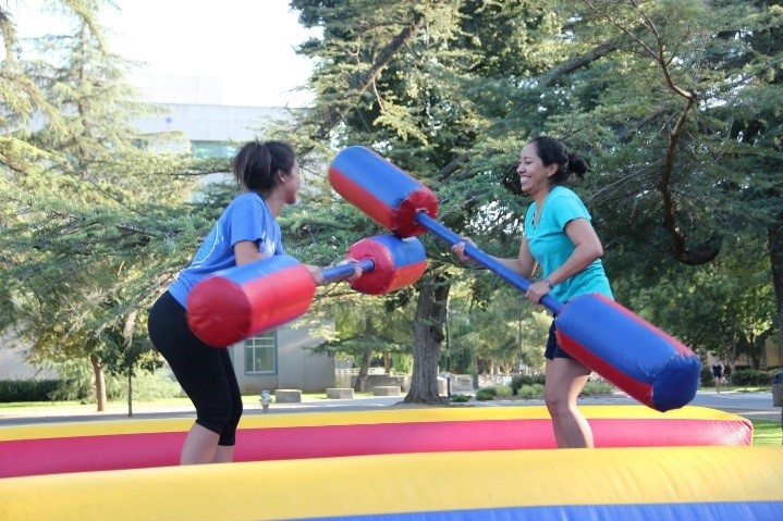 students jousting with padded sticks